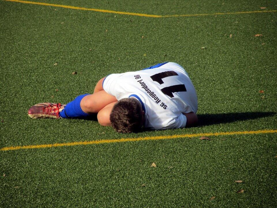 a soccer player suffering from Patellar Tendonitis injury lying in his side
