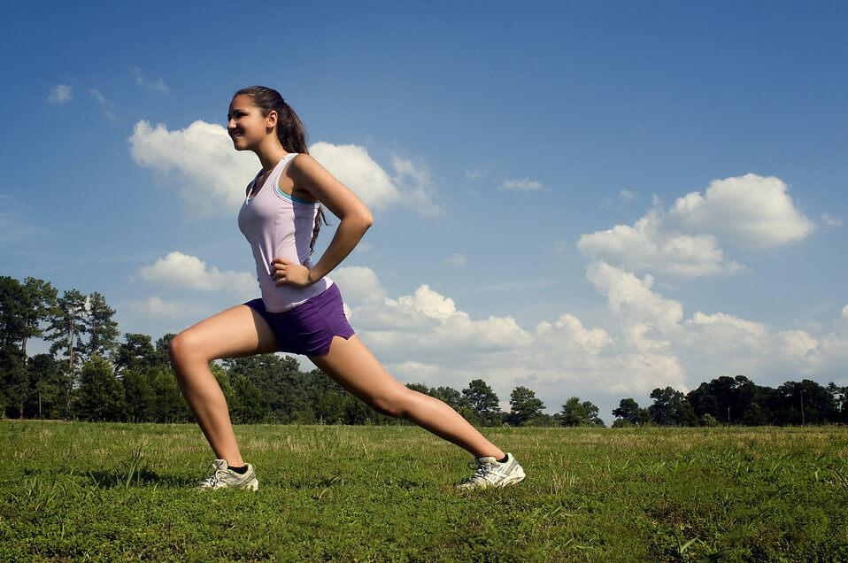A girl performing dynamic stretching to prevent Patellar Tendonitis