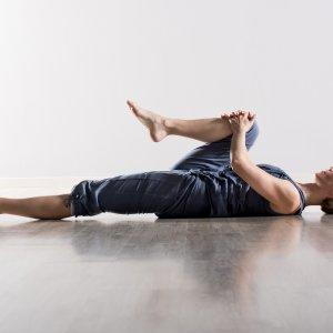 Woman lying on her back pulling one knee to her chest