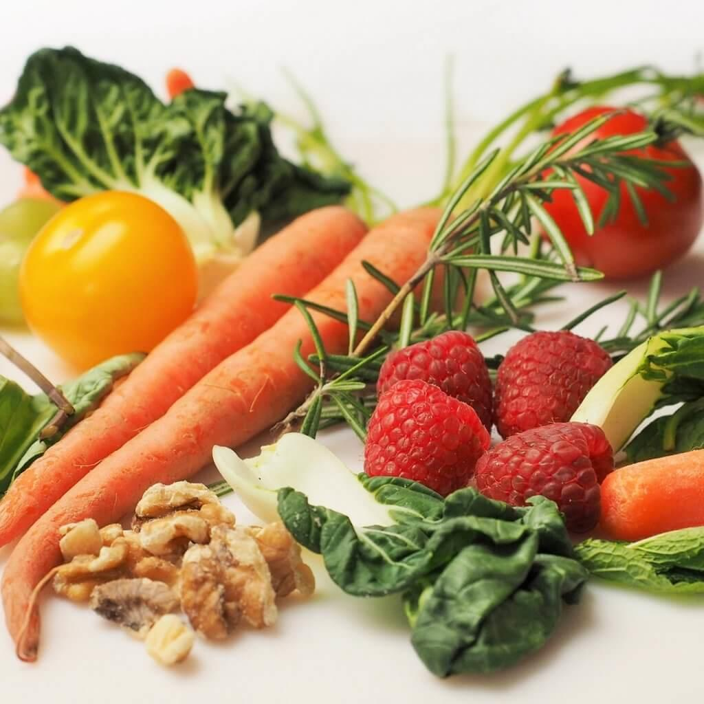 Picture of walnuts, carrots, raspberries, tomatoes, thyme, and greens