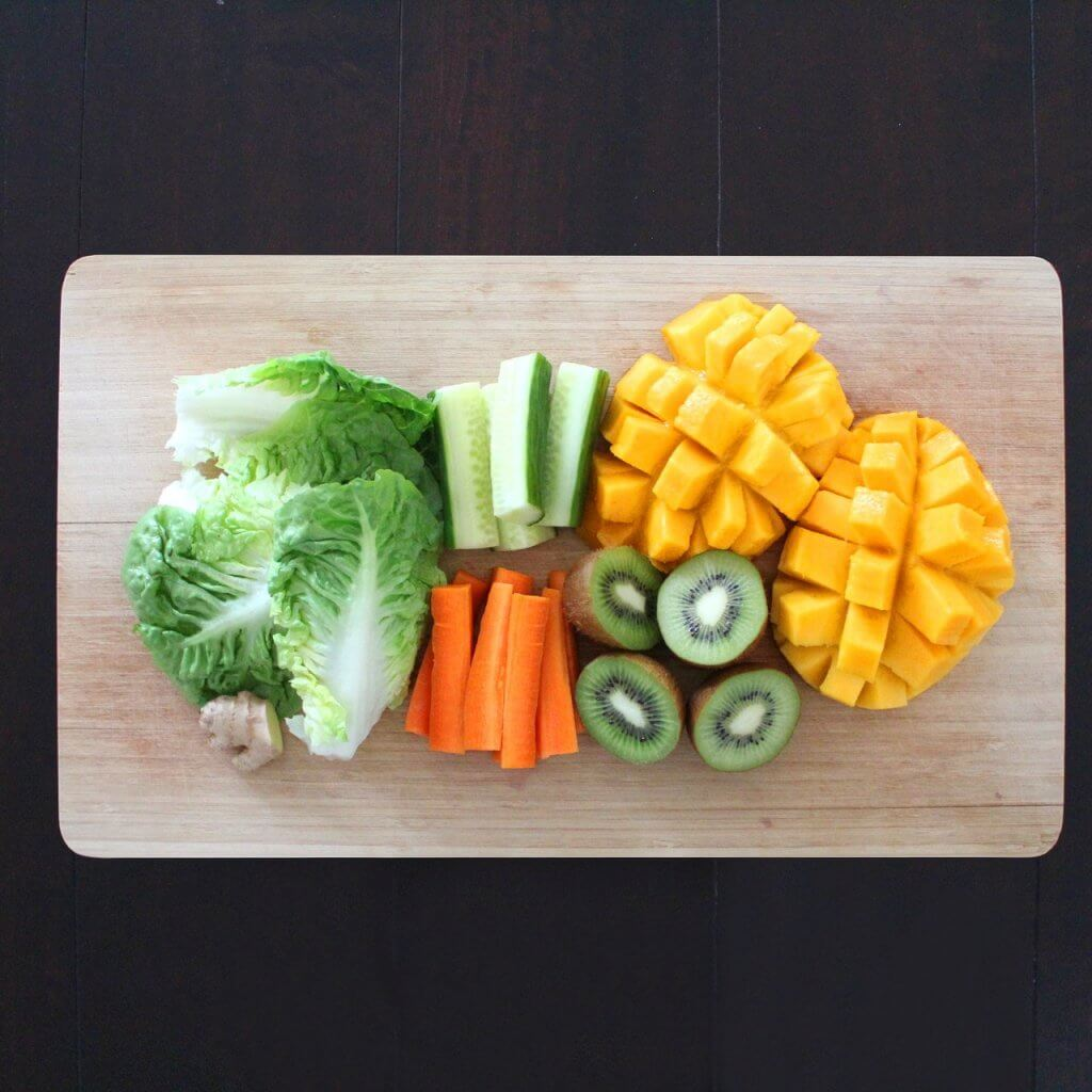 View from above of cutting board with chopped lettuce, cucumber, carrot, kiwi, and mango