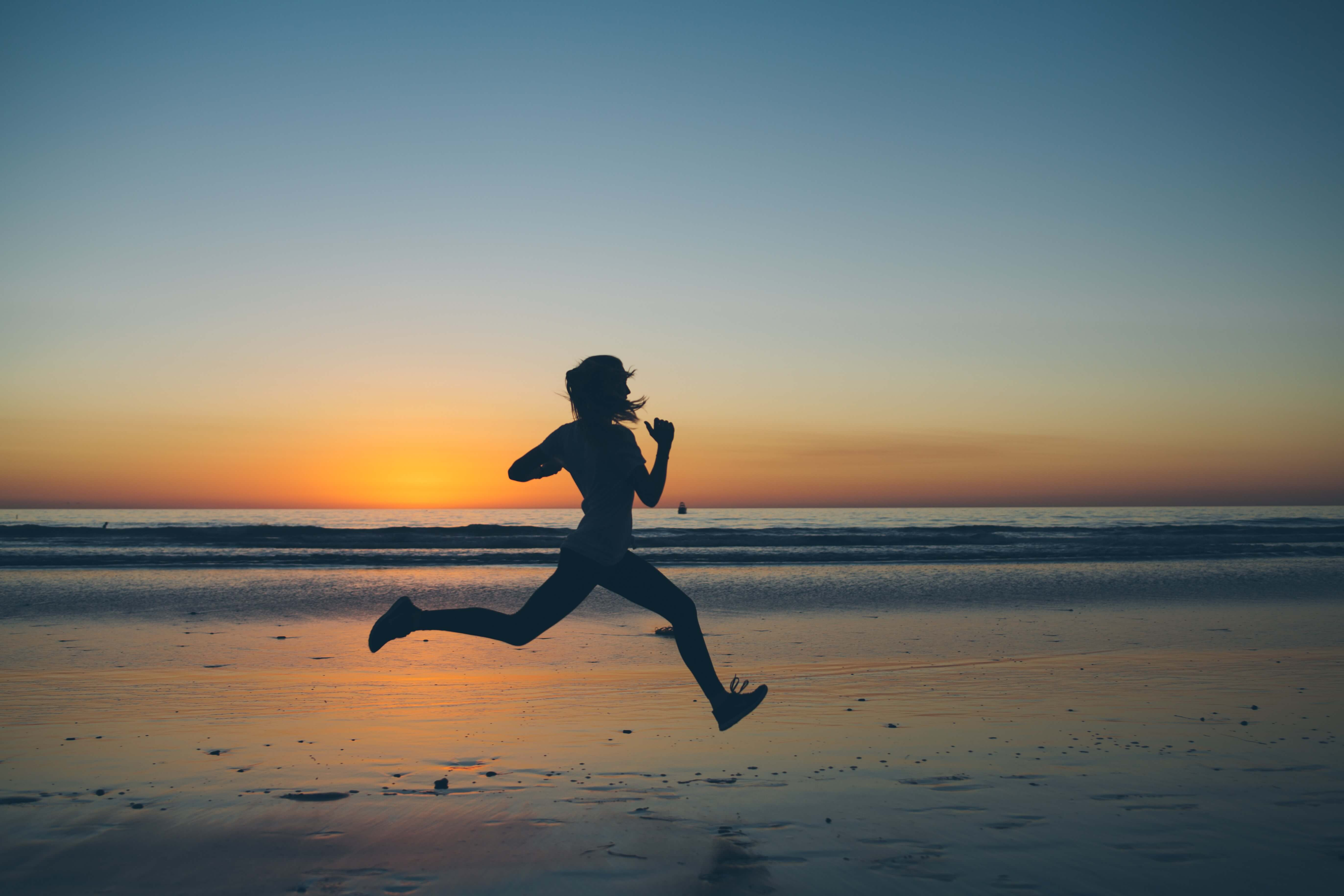 A runner on the beach at sunset