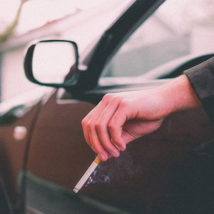 a driver's arm hanging out the car window holding a cigarette