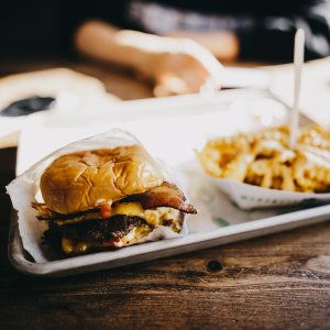 greasy hamburger and french fries on a tray
