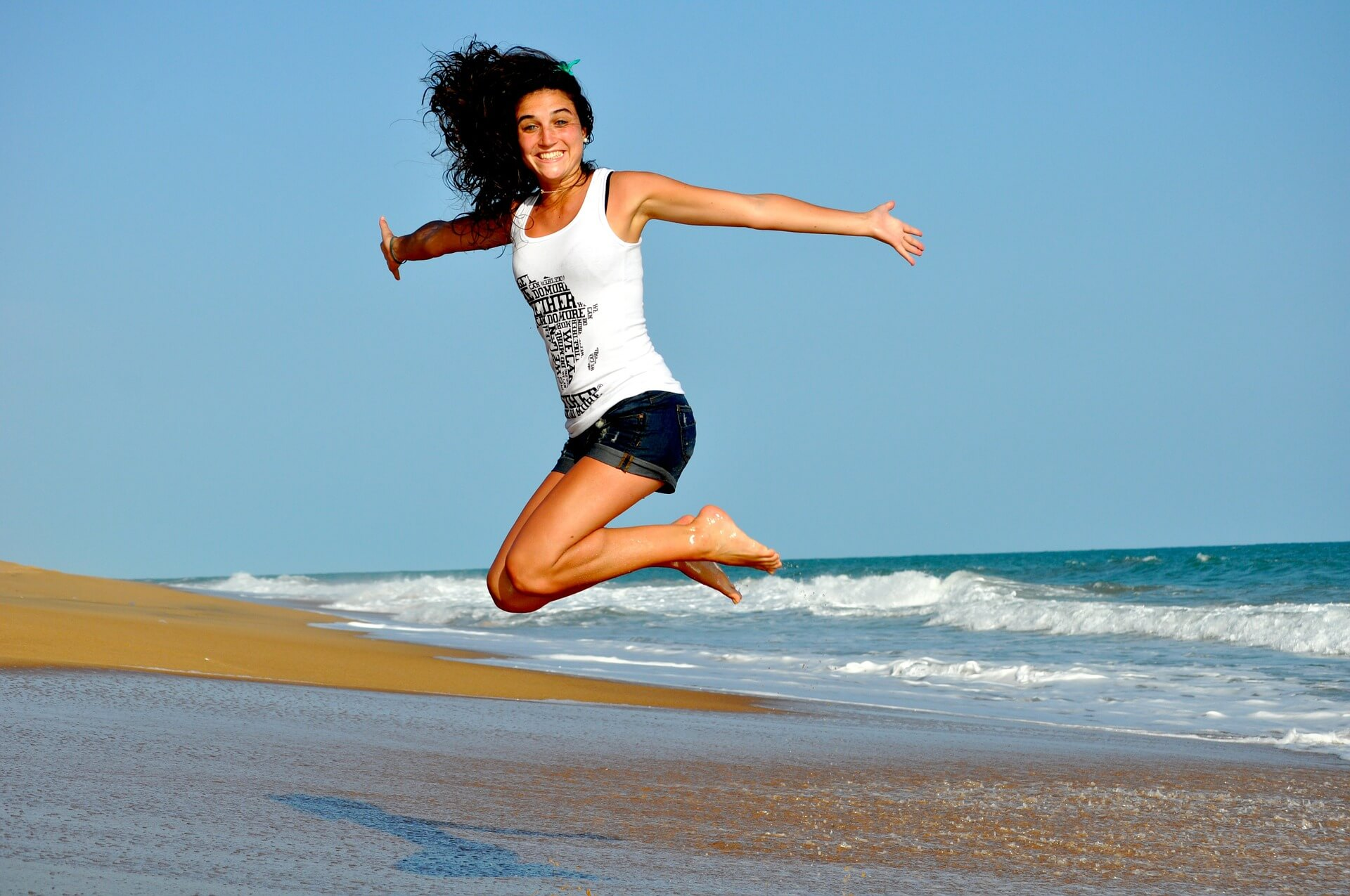 a young girl jumping in the air on a beach