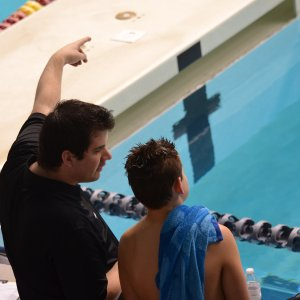 private coach for swimming instructing a child at the pool